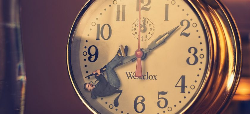 "alt=""man hanging from minute hand on old-fashioned alarm clock"""