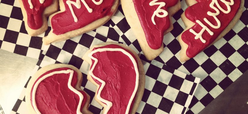 "alt=""three red broken heart-shaped cookies saying bite me & love hurts"""