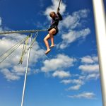 "alt=""girl in harness jumping up into the blue sky"""
