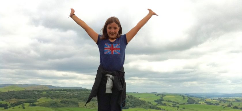 """alt=""""girl raising arms above her head over beautiful landscape"""""""