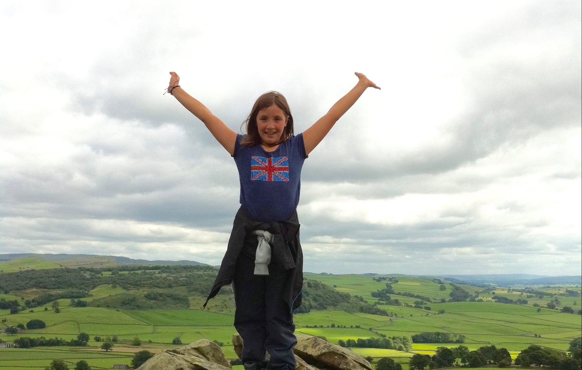 "alt=""girl raising arms above her head over beautiful landscape"""