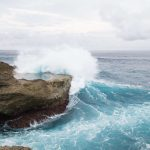 "alt=""ocean waves crashing against brown rock"""