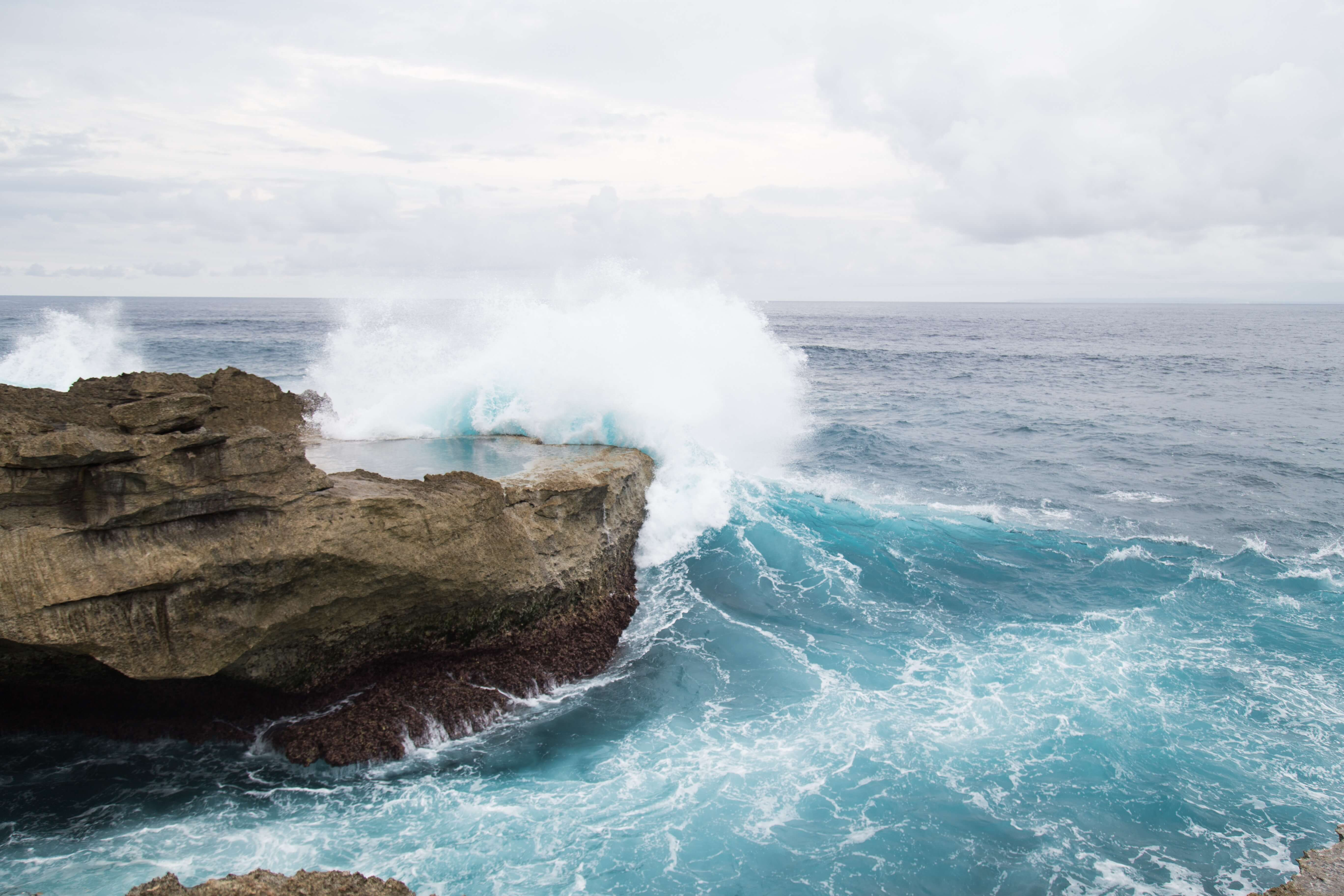 "alt=""ocean waves crashing against brown rock"""